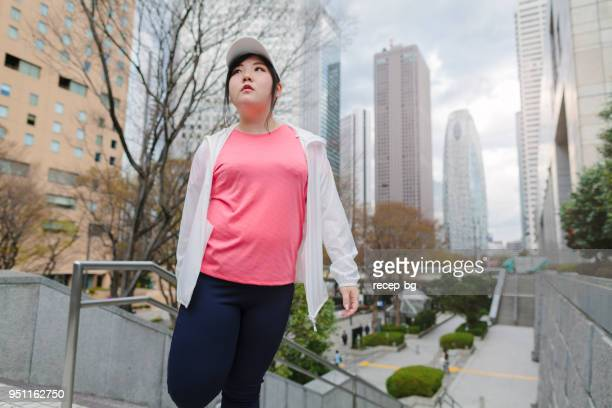 woman doing stretching in city - chubby asian woman stock pictures, royalty-free photos & images