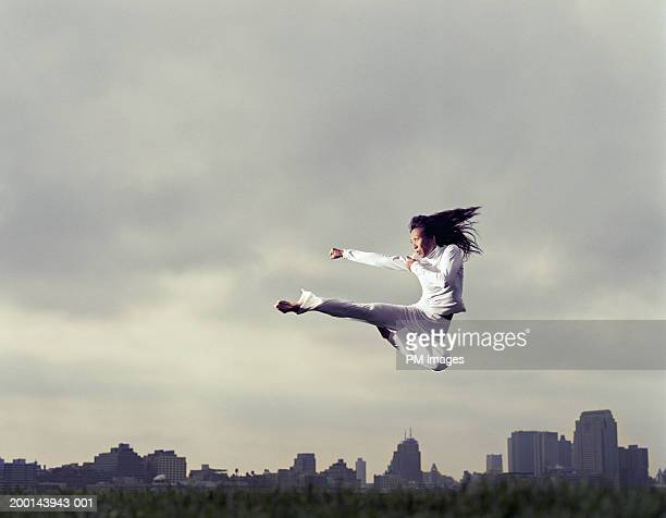 woman doing tae kwon do kick in park, low angle view - punching stock pictures, royalty-free photos & images