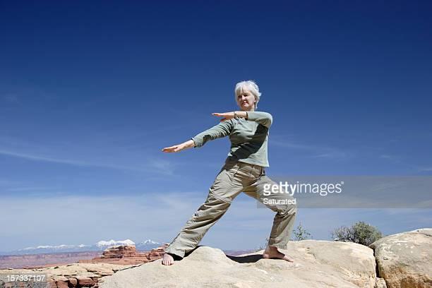 Woman Doing Tai Chi Against Desert Landscape