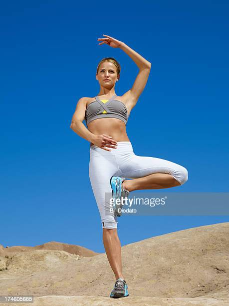 Woman doing tai chi tree pose outdoors