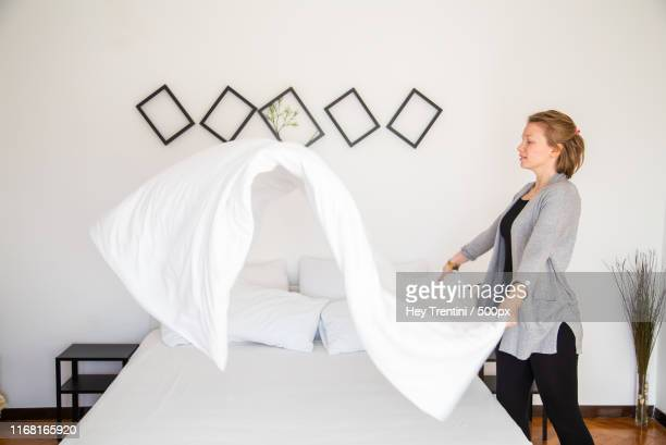 woman doing the bed in a authentic room - montar fotografías e imágenes de stock