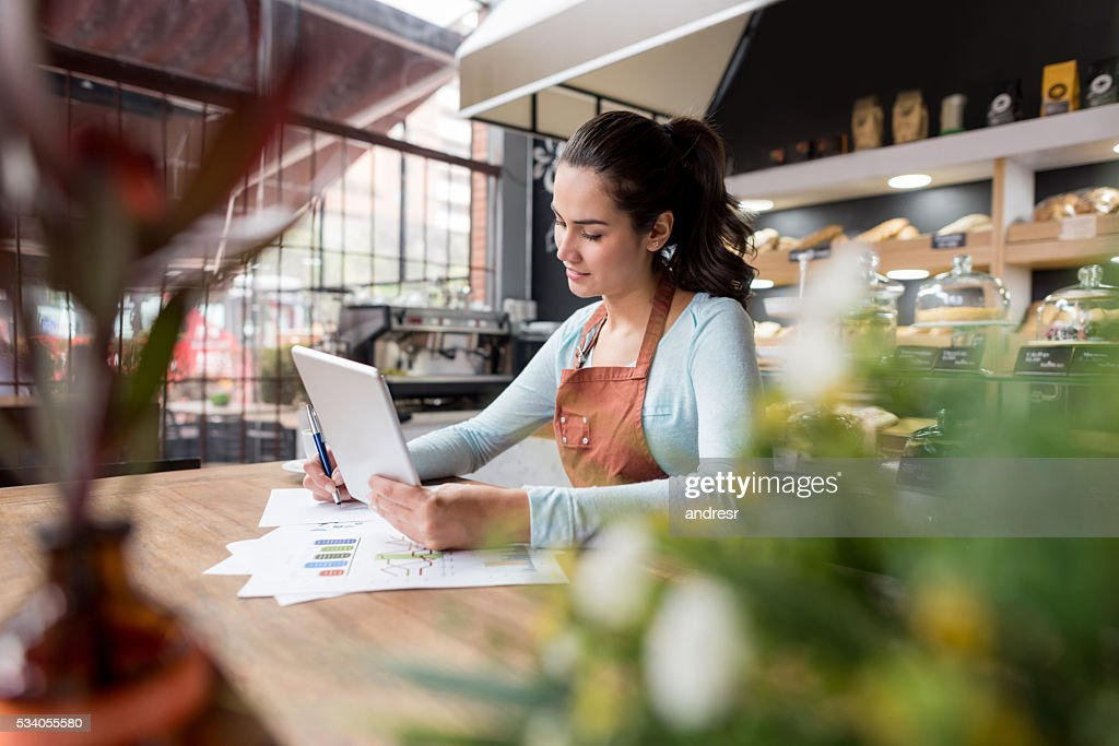 Woman doing the books at a restaurant : Stock Photo