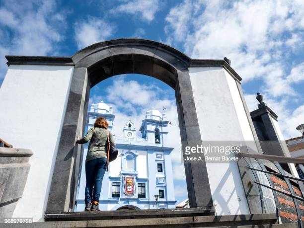 woman doing tourism and contemplating the misericordia church city of angra do heroismo, a unesco world heritage site, on terceira island in the azores, portugal. - las azores fotografías e imágenes de stock