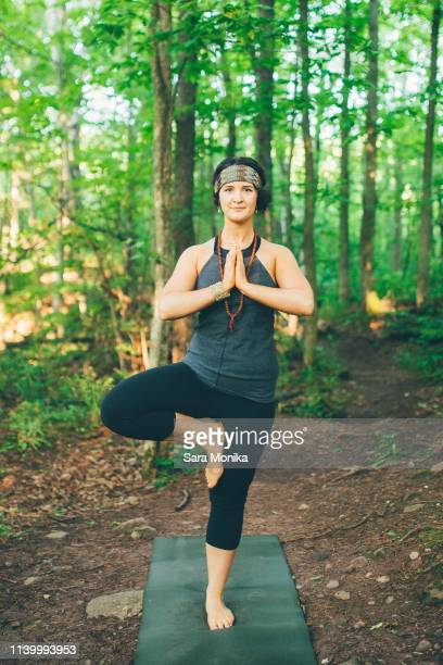 Woman doing tree pose in forest