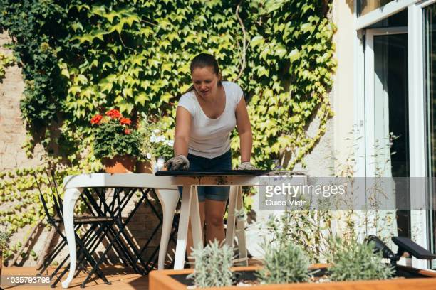 Woman doing upcycling with old table on garden deck.