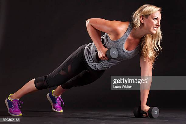 Woman doing upright rows in plank
