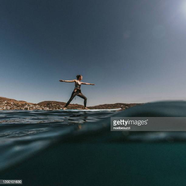 woman doing warrior 2 position on a paddleboard, laguna beach, california, usa - stability stock pictures, royalty-free photos & images