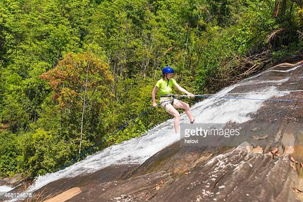 Femme cascade la descente en rappel