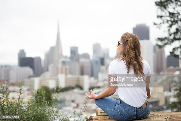 Woman Doing Yoga and facing the San Francisco Downtown