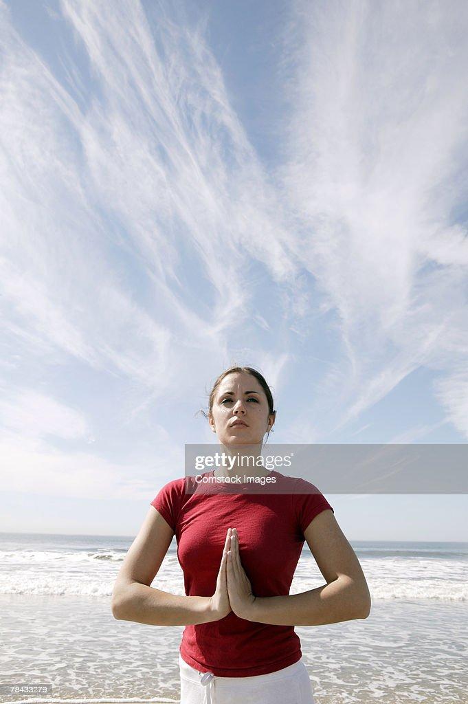 Woman doing yoga at beach : Stockfoto
