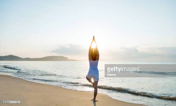 woman doing yoga at the beach - zen like stock pictures, royalty-free photos & images