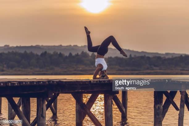 woman doing yoga at the lake - posizione descrittiva foto e immagini stock