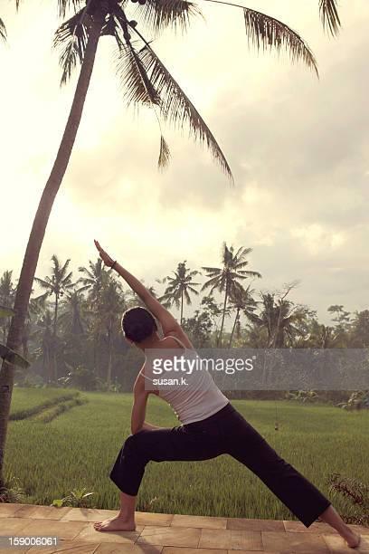 A woman doing yoga by peaceful padi field.