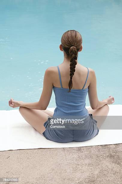 Woman doing yoga by pool