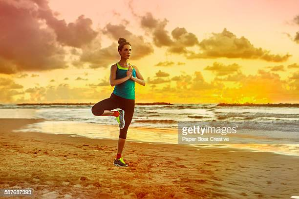 woman doing yoga by the beach during sunset - harriet stock photos and pictures