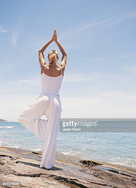 Woman Doing Yoga By the Edge of the Sea