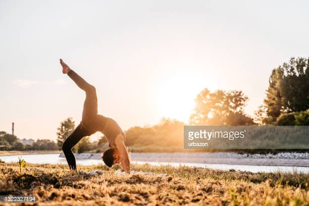 woman doing yoga by the river at sunset - riverbank stock pictures, royalty-free photos & images