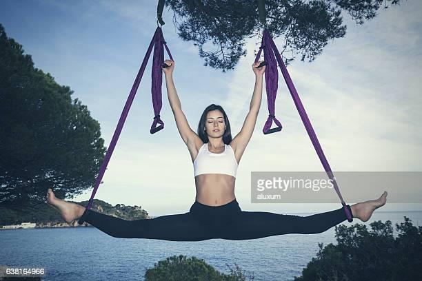 woman doing yoga exercises at the sea - split acrobatiek stockfoto's en -beelden