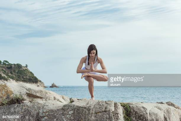 Woman doing yoga exercises at the sea