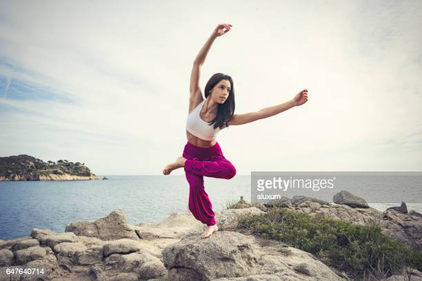 woman doing yoga exercises at the sea - yogi stock photos and pictures