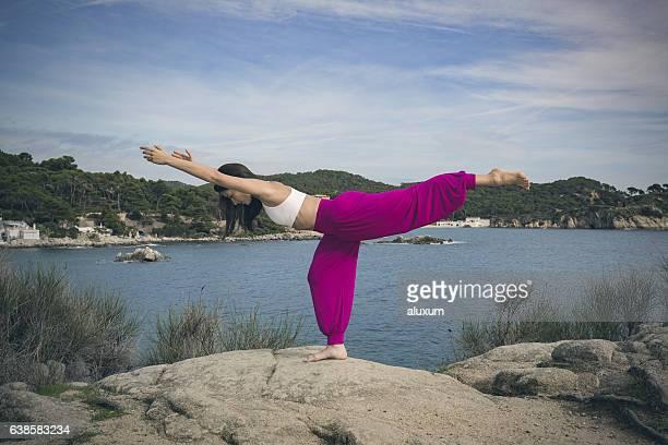 woman doing yoga exercises at the sea warrior 3 pose - amputee woman stock-fotos und bilder