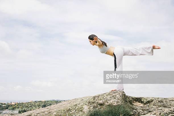 Woman doing yoga exercises on a mountain