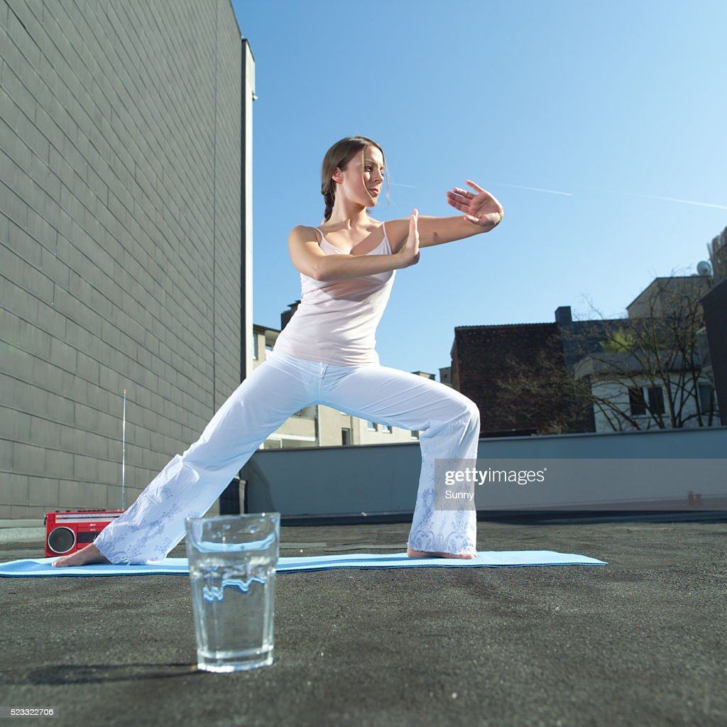 woman doing yoga exercises on flat roof ストックフォト getty images
