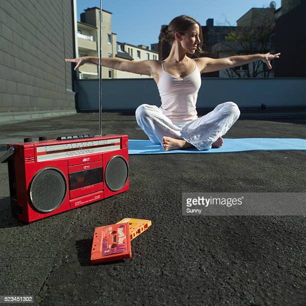 Woman Doing Yoga Exercises on Flat Roof