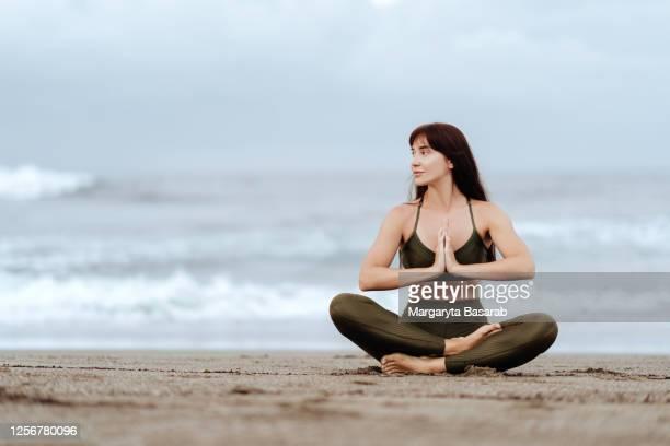 woman doing yoga exercises beach summer