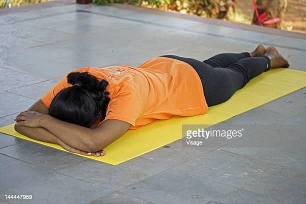 a woman doing yoga exercises - acostado boca abajo fotografías e imágenes de stock