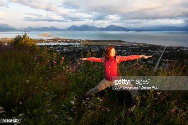 a woman doing yoga in a meadow with a view of homer spit, kachemak bay and the kenai mountains in the background - kachemak bay stock pictures, royalty-free photos & images