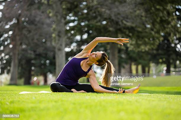 A woman doing yoga in a park.