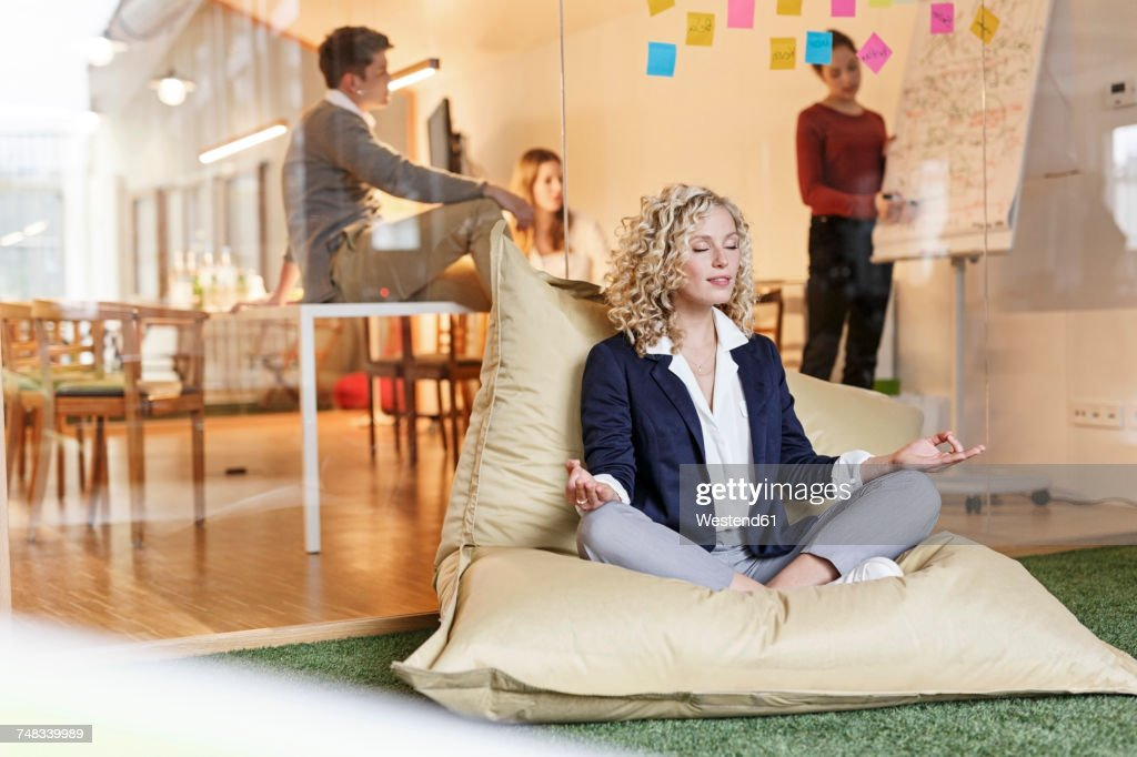 Woman doing yoga in bean bag with meeting in background : Stock-Foto