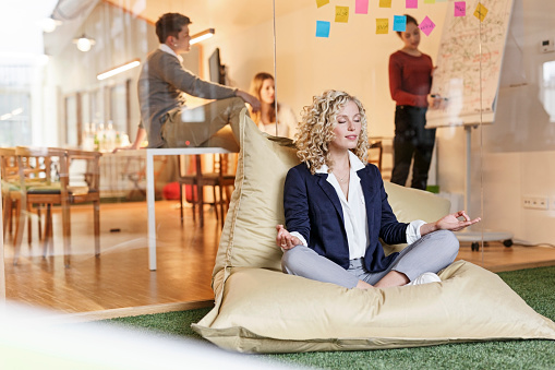 Woman doing yoga in bean bag with meeting in background - gettyimageskorea
