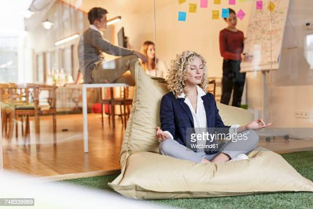 woman doing yoga in bean bag with meeting in background - meditieren stock-fotos und bilder
