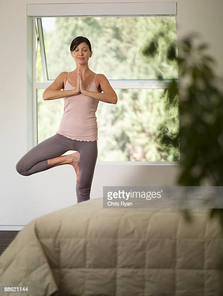 woman doing yoga in bedroom - tree position stock photos and pictures