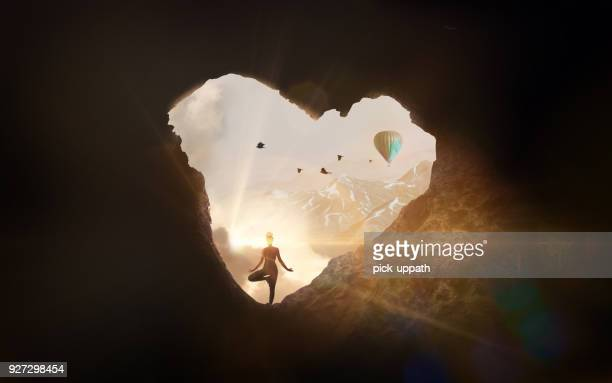 Woman doing yoga in cave shaped like a heart