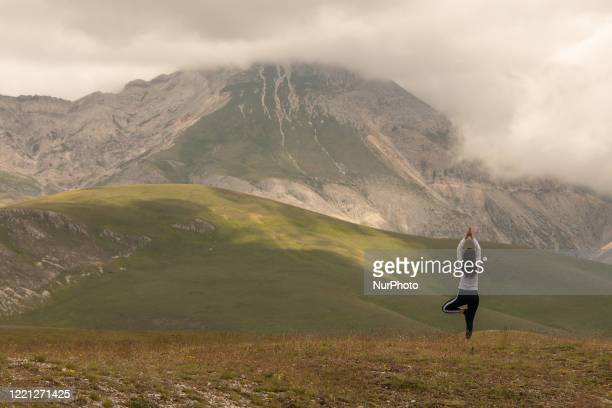 Woman doing yoga in Gran Sasso Park , L'Aquila, Italy on June 20, 2020. On June 21 the whole World celebrates this day 'International Day of Yoga'...