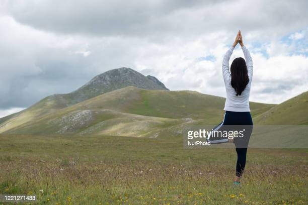A woman doing yoga in Gran Sasso Park L'Aquila Italy on June 20 2020 On June 21 the whole World celebrates this day 'International Day of Yoga'...