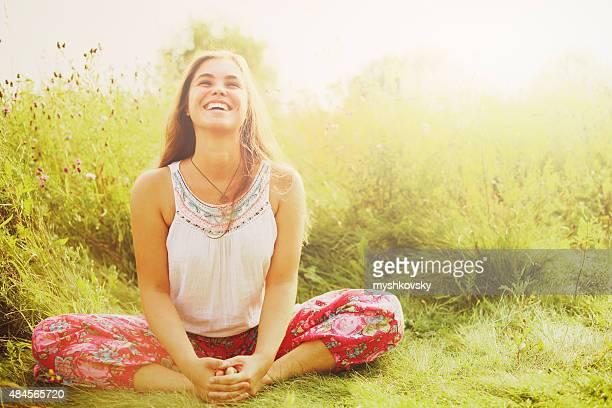 Mulher fazendo yoga em relva.