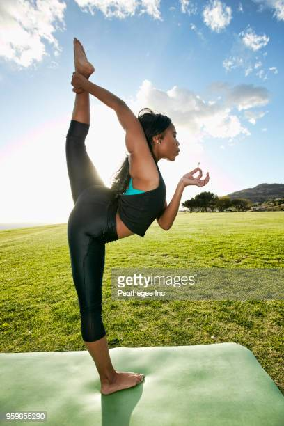 woman doing yoga in green field - yoga pants stock photos and pictures