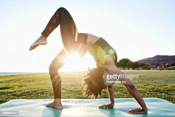 woman doing yoga in green field - yoga stock pictures, royalty-free photos & images
