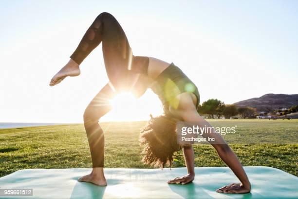 woman doing yoga in green field - sol - fotografias e filmes do acervo