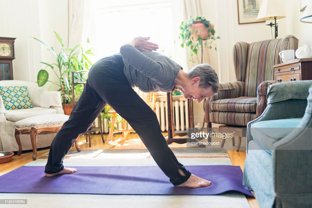60+ woman doing yoga in living room : Stock Photo