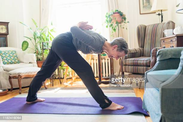 60+ woman doing yoga in living room