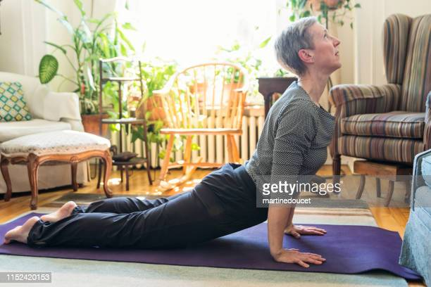 "60+ woman doing yoga in living room - ""martine doucet"" or martinedoucet stock pictures, royalty-free photos & images"