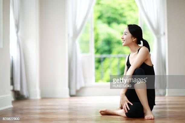 woman doing yoga in living room - スポーツウェア ストックフォトと画像