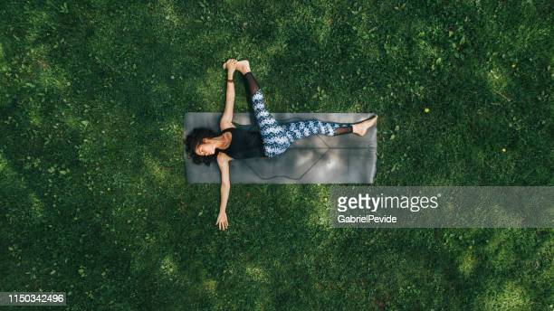 woman doing yoga in the park - yoga stock pictures, royalty-free photos & images
