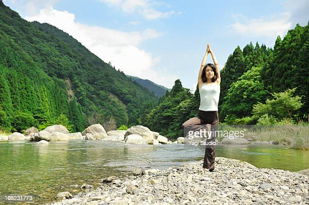Woman doing yoga in the river