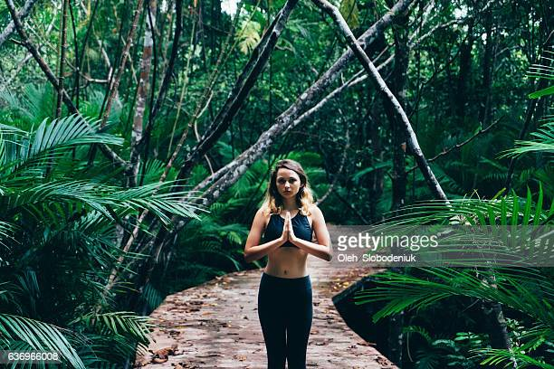 Woman doing yoga in topical forest
